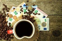 Grains de café rôtis et euro billets de banque valides Commerce de café Vente des marchandises photographie stock