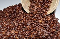 Grains de café rôtis et un bidon en bois photos stock