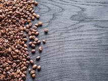 Grains de café rôtis sur le vieux fond en bois Vue supérieure Image stock