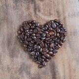 Grains de café rôtis, symbole de coeur sur le fond en bois Photos stock