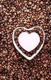 Grains de café rôtis avec la feuille de papier en forme de coeur au-dessus du café b Image libre de droits