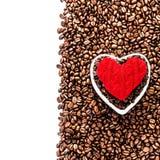 Grains de café rôtis avec le coeur rouge au-dessus du fond de grains de café Photographie stock libre de droits