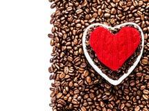 Grains de café rôtis avec le coeur rouge au-dessus du fond de grains de café Photo libre de droits