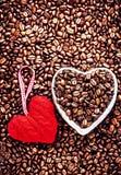 Grains de café rôtis avec le coeur rouge au-dessus du fond de grains de café Image stock