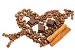 Grains de café rôtis dans la forme du coeur avec la flèche de cupidon, cubes en chocolat, bâton de cannelle, d'isolement sur le f Image stock