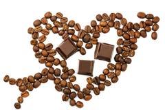 Grains de café rôtis dans la forme du coeur avec la flèche de cupidon, cubes foncés en chocolat, d'isolement sur le fond blanc, v Photos libres de droits