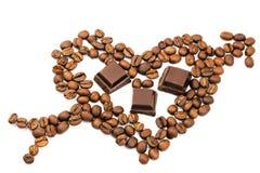 Grains de café rôtis dans la forme du coeur avec la flèche de cupidon, cubes foncés en chocolat, d'isolement sur le fond blanc Images libres de droits