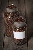 Grains de café rôtis dans un pot cristal sur le fond en bois photographie stock libre de droits