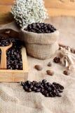 Grains de café rôtis sur le fond de brun de sac Photos stock