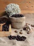 Grains de café rôtis sur le fond de brun de sac Image stock