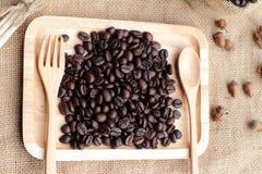 Grains de café rôtis sur le fond de brun de sac Photographie stock libre de droits