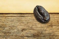 Grains de café rôtis sur le vieux papier sur le fond en bois Photographie stock