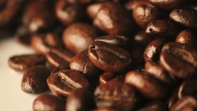 Grains de café renversés tournants en gros plan banque de vidéos