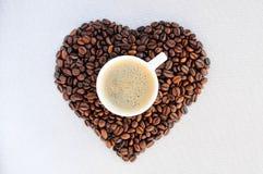 Grains de café sous forme de coeur et tasse de café fraîchement préparé Photos libres de droits