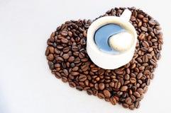 Grains de café sous forme de coeur et tasse de café fraîchement préparé Fond de jour du ` s de Valentine de café Images stock