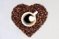 Grains de café sous forme de coeur et tasse de café fraîchement préparé Fond de jour du ` s de Valentine de café Image libre de droits
