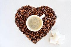 Grains de café sous forme de coeur et tasse de café fraîchement préparé Fond de jour du ` s de Valentine de café Photos stock