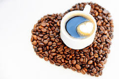 Grains de café sous forme de coeur et tasse de café fraîchement préparé Fond de jour du ` s de Valentine de café Photographie stock libre de droits