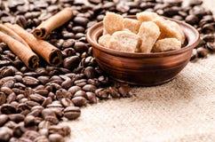 Grains de café, sucre de canne et cannelle sur la table Images stock