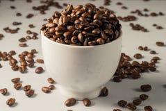 Grains de café sur Gray Background neutre Café foncé de rôti blanc Images stock