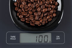 Grains de café sur l'échelle de cuisine Photos stock