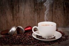 Grains de café sur la vieille table en bois avec la tasse et la fumée de café Image libre de droits
