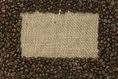 Grains de café sur le fond de jute photos stock