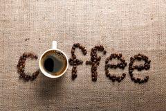 Grains de café sur le fond de toile de jute Image stock