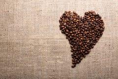 Grains de café sur le fond de toile de jute Photographie stock libre de droits