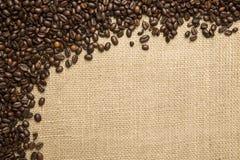 Grains de café sur le fond des tissus de jute Photographie stock libre de droits