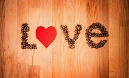 Grains de café sur le fond en bois Forme de l'amour de mot faite à partir des grains de café, décorés du coeur rouge sur la surfa Photos libres de droits