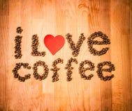Grains de café sur le fond en bois Forme de l'amour de mot faite à partir des grains de café, décorés du coeur rouge sur la surfa Photos stock