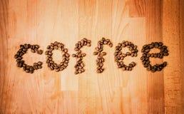 Grains de café sur le fond en bois Forme de l'amour de mot faite à partir des grains de café, décorés du coeur rouge sur la surfa Photo stock