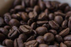 Grains de café sur un tas dans une tasse Foyer sélectif Images stock