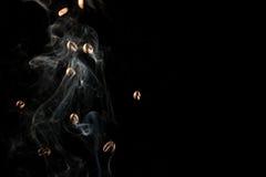 Grains de café tombant vers le bas fumée de cuvette au-dessus du fond noir - d'isolement Images libres de droits
