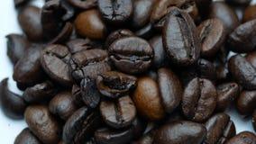 Grains de café tournant sur le fond blanc banque de vidéos