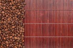 Grains de café se trouvant sur un tapis en bambou Image libre de droits