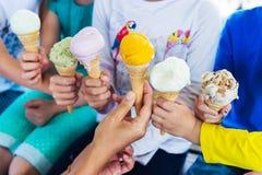 6 grains de crème glacée colorée se tenant par des enfants Images stock