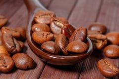 Grains de plan rapproché de café Des grains de café sont situés sur une cuillère a Photos stock