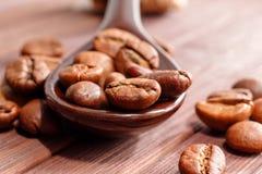 Grains de plan rapproché de café Des grains de café sont situés sur une cuillère a Images stock