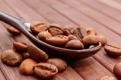 Grains de plan rapproché de café Des grains de café sont situés sur une cuillère a Photo stock