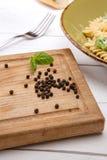 Grains de poivre dessus sur la planche en bois Photo stock