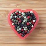 Grains de poivre mélangés dans une cuvette de coeur Photographie stock libre de droits