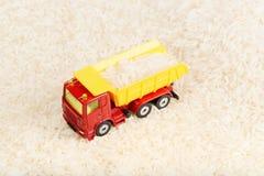 Grains de riz transportés par jouet de camion à benne basculante Images stock