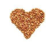 Grains de sarrasin sous forme de coeur sur un fond blanc Photographie stock libre de droits