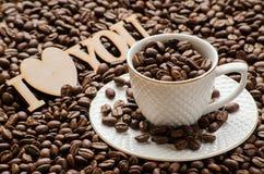 Grains dispersés de café, de tasse avec la soucoupe et d'un plat en bois Photographie stock libre de droits