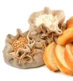 Grains et farine de blé dans les sacs à tissu et les morceaux de pain frais Images stock