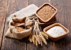 Grains, flour and wheat ears on a wooden table stock photos