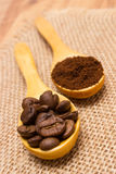 Grains and ground coffee with wooden spoon on jute canvas Royalty Free Stock Images