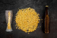 Grains of malting barley near beer bottle and glass on black background top view. Grains of malting barley near beer bottle on black background top view Stock Images
